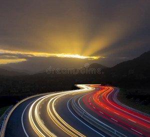 coucher-du-soleil-avec-des-lumières-de-voiture-sur-la-route-51616127